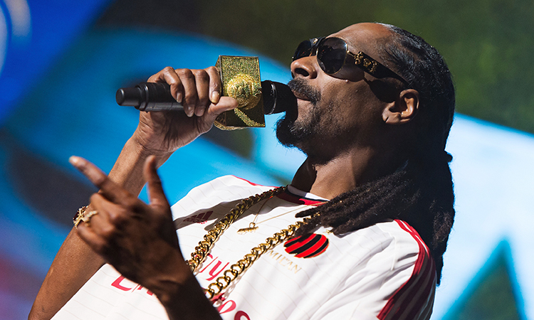 Snoop Dogg holding microphone and rapping at concert
