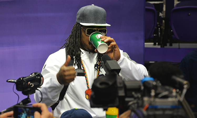 Marshawn Lynch drinking from cup at press conference