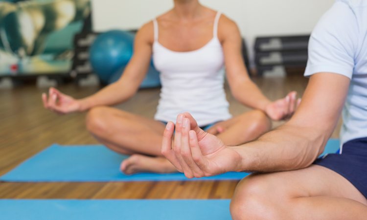 Couple sitting in lotus pose at a fitness studio