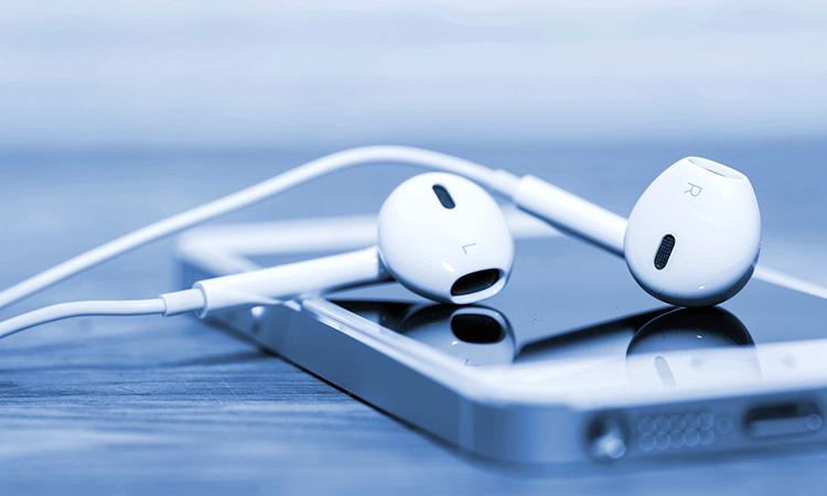 White earbud headphones draped across a smartphone