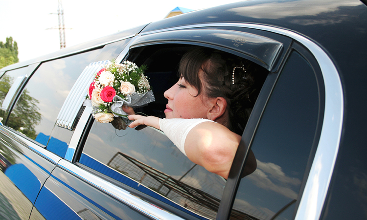 Bride holding bouquet with head out the window of limousine