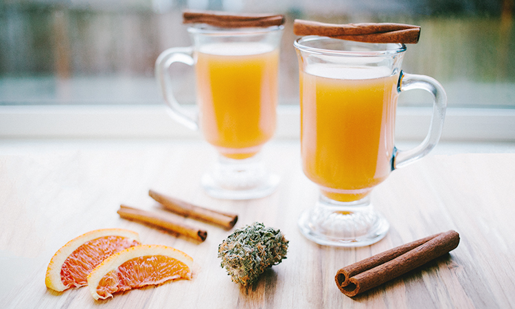 Apple cider infused with cannabis on a wooden table with cinnamon sticks, orange wedges, and cannabis flower