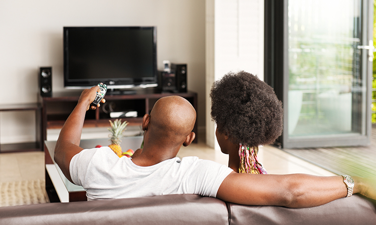 A couple sitting on the couch watching television