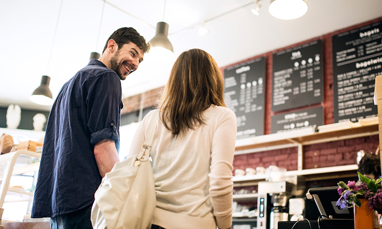 A couple standing in line at a coffee shop