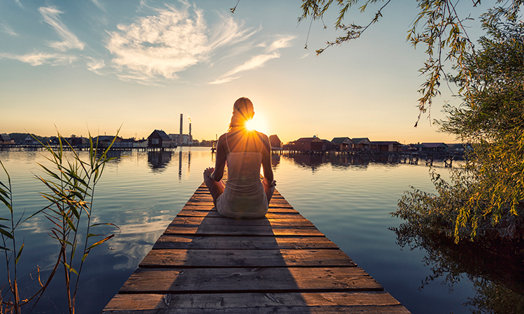 Woman meditating on lake dock at sunset