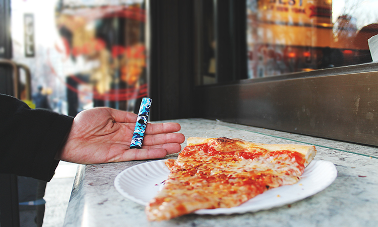 Hand holding cannabis vaporizer next to slice of pizza outside Joe's Pizza in NYC