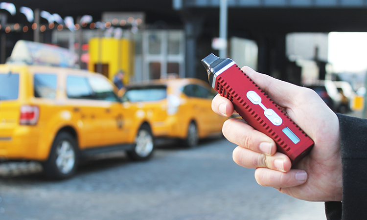 Hand holding cannabis vaporizer with New York City cabs on street in background