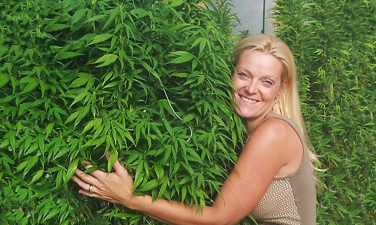 Toni Savage Fox, founder of 3D Cannabis Center, hugging cannabis plants