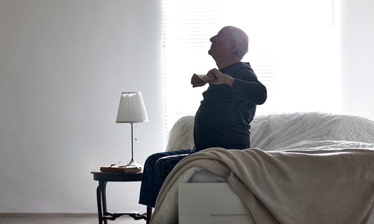 Elderly man sitting on bed and stretching arms