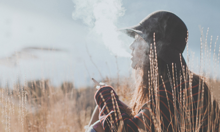 Woman smoking cannabis joint in mountains