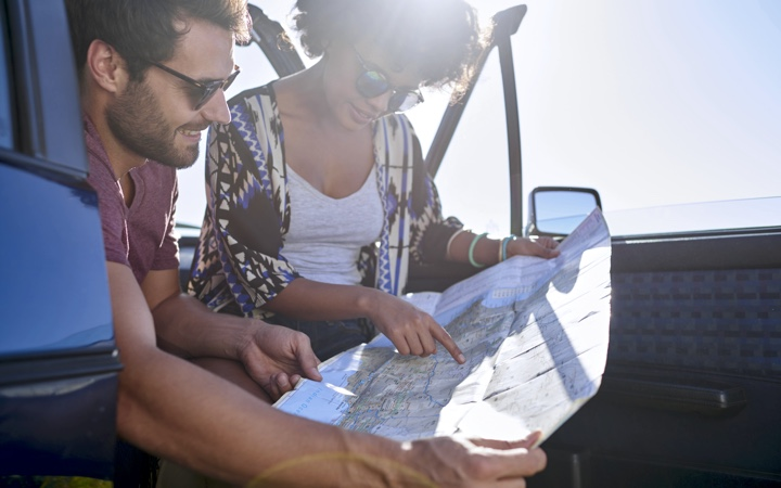 Couple on a road trip checking their map