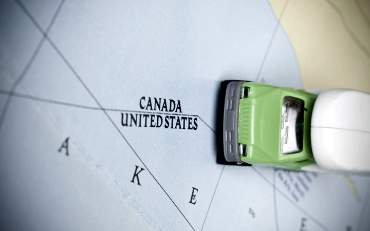 Canada - U.S. map border with a little toy car
