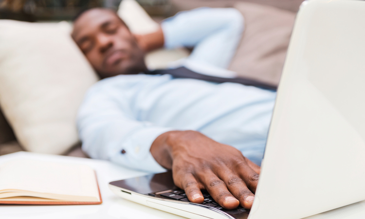 A man sleeping on a couch behind a laptop