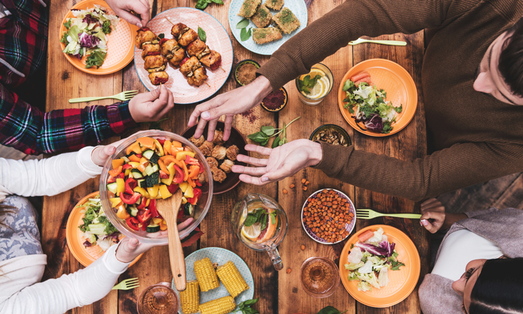 Friends eating at large table of food