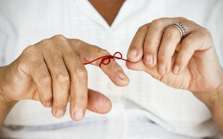 Reminder string tied around a finger