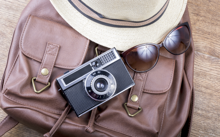 Purse with a camera, hat, and sunglasses