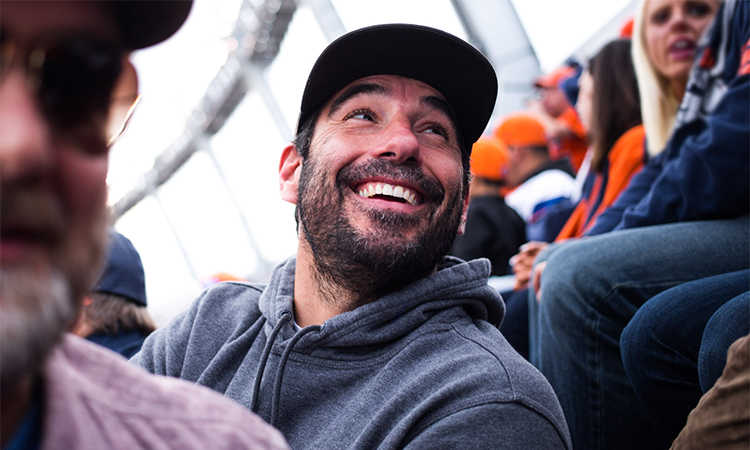 Former NFL player Nate Jackson laughing with friends at the Denver Broncos game with Leafly