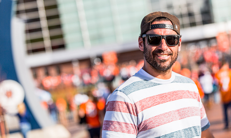 Former NFL player Nate Jackson smiling at a tailgate for the Denver Broncos with Leafly