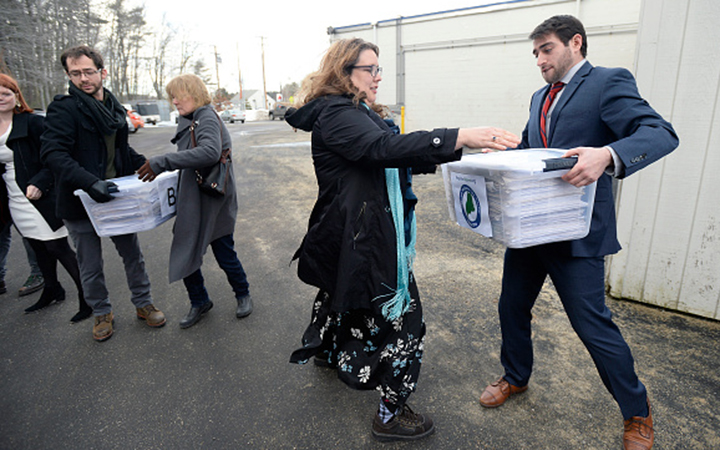 Campaign manager David Boyer passes a box of petitions to Rep. Diane Russell from Portland on Feb. 1, as the Campaign to Regulate Marijuana Like Alcohol prepares to deliver the petitions to Augusta. Photo via Getty