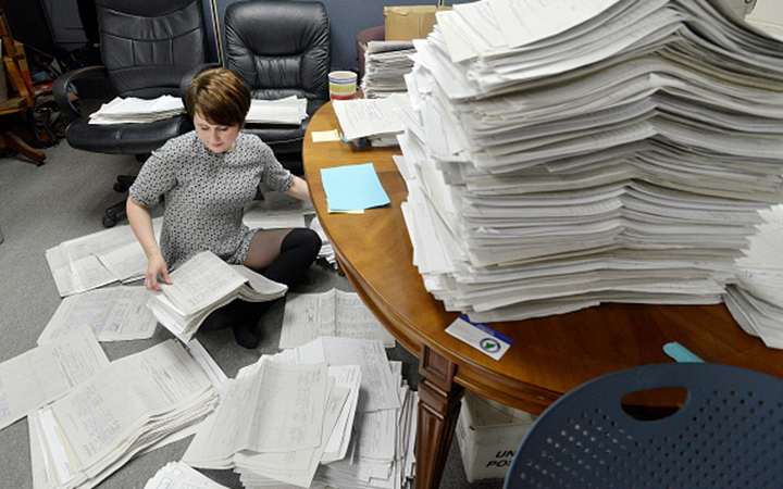 Staff and volunteers for the legalization campaign are sort petitions at an office in Falmouth, Maine. Photo via Getty