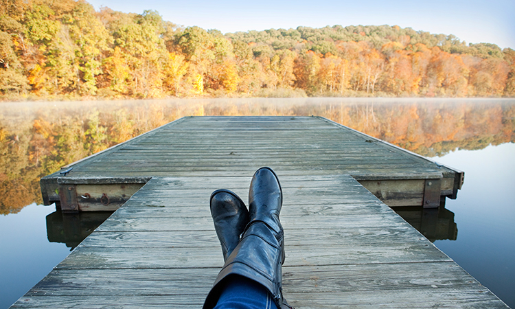 Person relaxing on lakeside dock in autumn