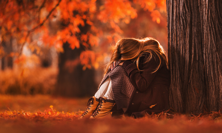 Girl hanging head down in park with beautiful autumn leaves in background