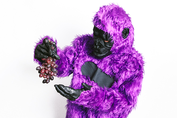 Person holding grapes and wearing a purple ape costume