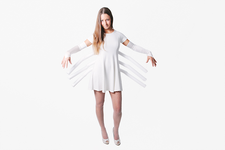 """Woman wearing white dress with white """"spider legs"""" attached for costume"""