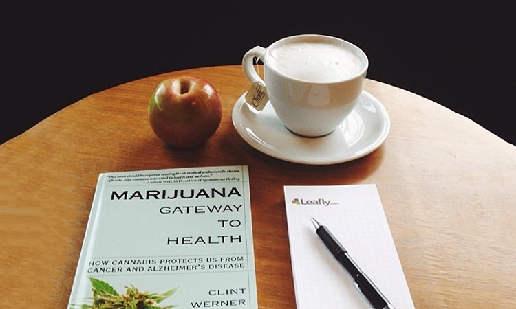 "Table with coffee, an apple, a ""Marijuana: Gateway to Health"" book, and a Leafly notepad"