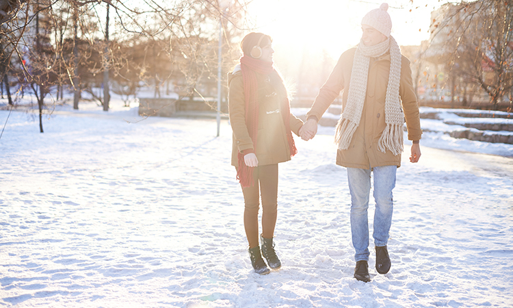 Couple walking in winter coats through a snow-covered park