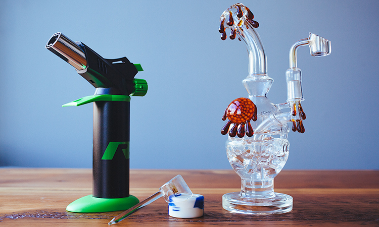 "Cannabis concentrate ""dabbing"" tools: small blow torch, concentrate container, and glass dab rig"