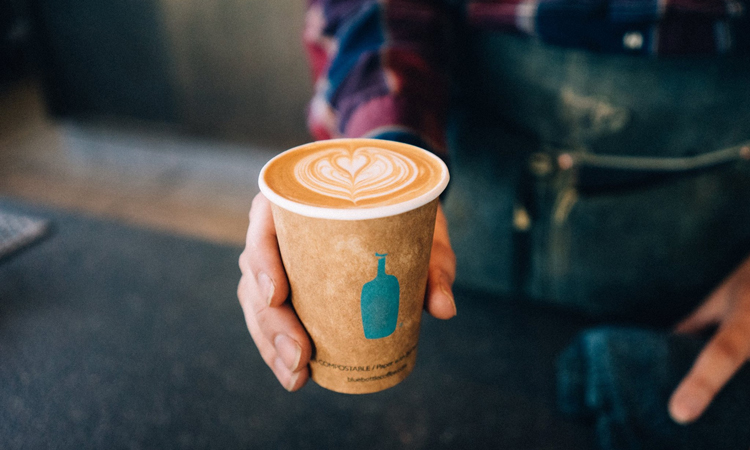 Man holding latte from Blue Bottle Coffee