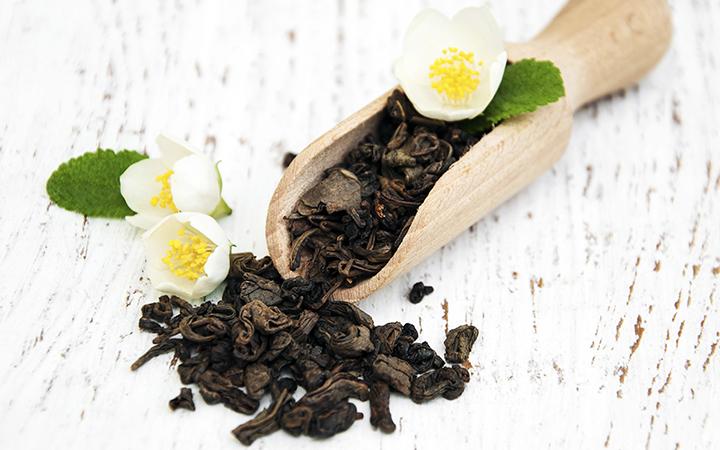 Dry green tea leaves with jasmine flowers
