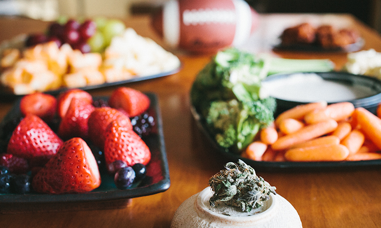 A spread of snacks and cannabis on a table with a football in the background