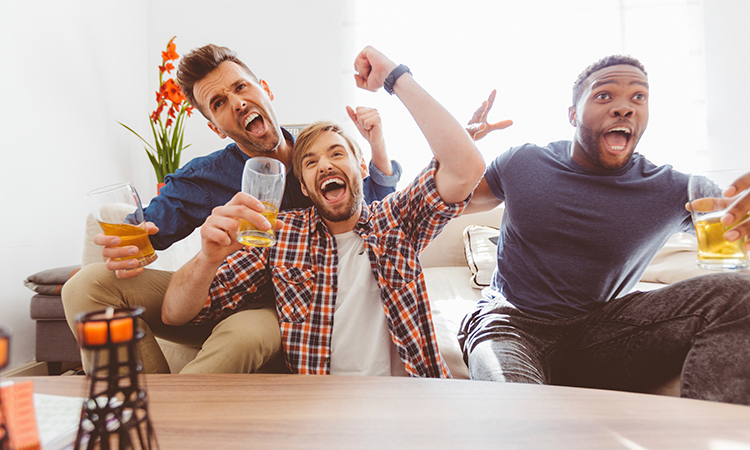 Three men in blue and orange cheering while watching football