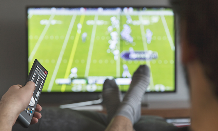 A person on couch holding a remote and watching football