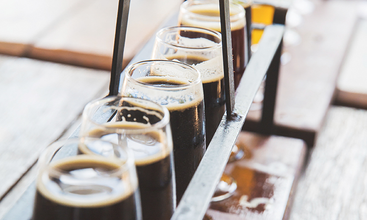 A flight of beers on a table arranged from dark to light brew