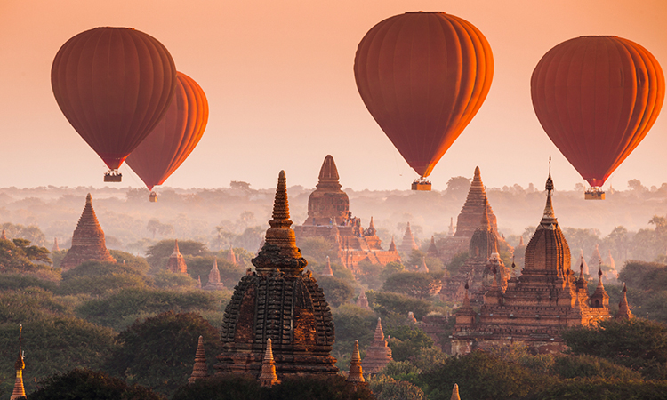 Balloons flying over ruins in Myanmar, Burma, at sunrise