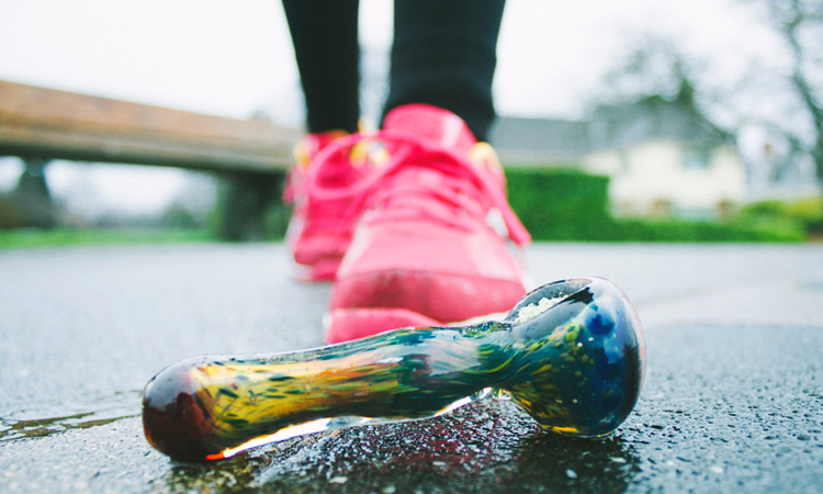 Glass hand pipe in front of a woman wearing running shoes