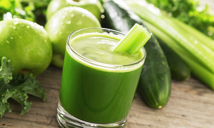 Glass of green juice near green vegetables