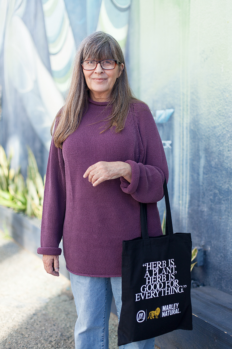 Jeannie Herer, wife of the late cannabis advocate Jack Herer, holding a Marley Natural tote bag