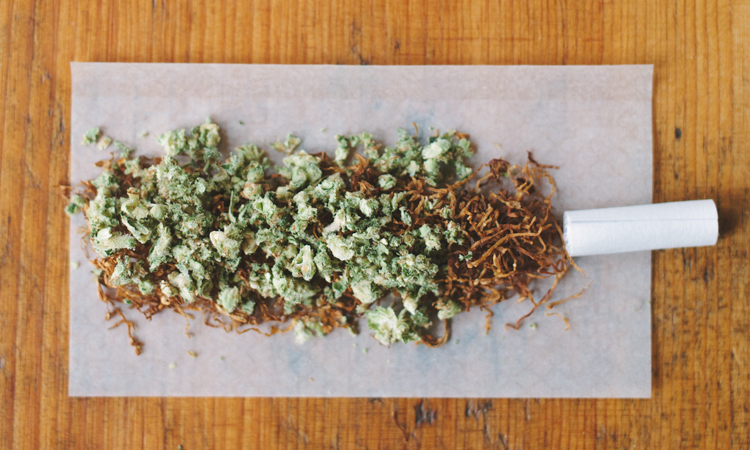 Ground cannabis sprinkled on top of loose leaf tobacco in an open rolling paper with a paper crutch
