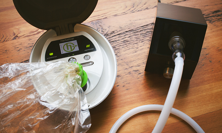 Two table-top cannabis vaporizers on a wooden table