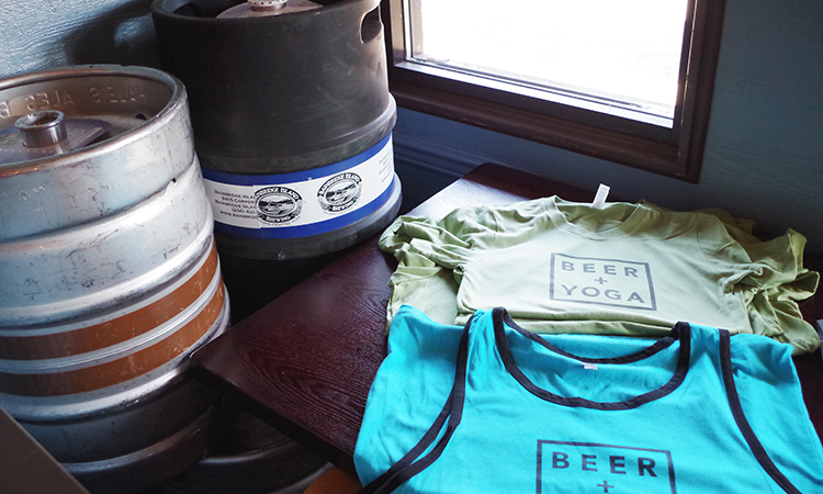 Beer + Yoga t-shirts next to kegs