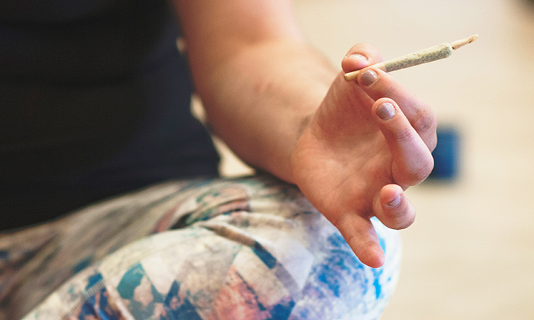 Woman holding annabis joint while doing yoga
