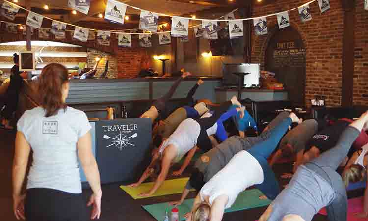 Group of people doing yoga at beer bar