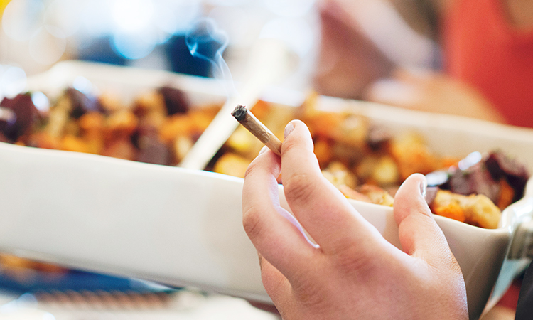 Hand holding burning joint near table of food